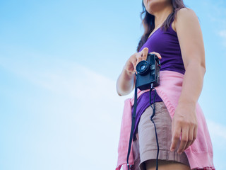 Pretty woman is a professional photographer with retro film camera blue sky background