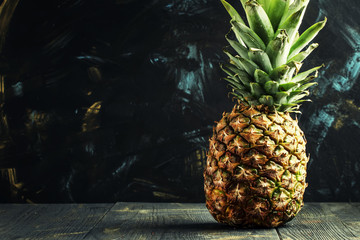 Fresh pineapple, dark wood background, selective focus