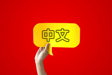 Human Hands Holding 'Zhongwen' Yellow Speech Bubble Over Red Background - Zhongwen means Chinese language