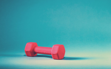 Pink dumbbell on a blue background