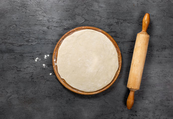 Wall Mural - Pizza dough on round wooden board with rolling pin