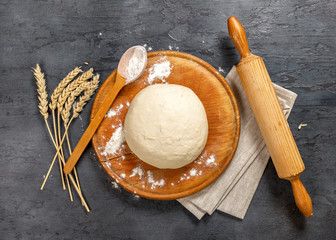 Wall Mural - Dough with ears of wheat, rolling-pin and spoon with flour