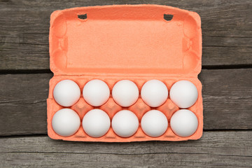 Carton of organic eggs on wooden background with instant photograph. Top view.