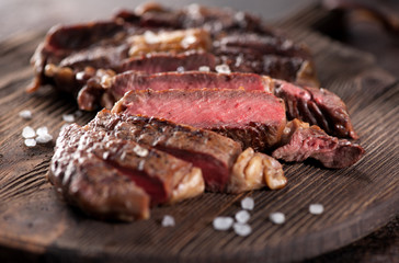 Sliced medium rare grilled beef steak ribeye close-up on a brown rusty background