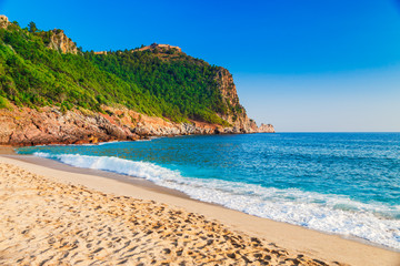 Cleopatra beach on sea coast with green rocks in Alanya peninsula, Antalya district, Turkey. Beautiful sunny landscape for tourism with clear water and sand. Alanya Castle on the cliff
