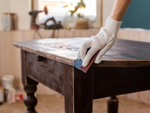 Restoration of old wooden table with abrasive paper.