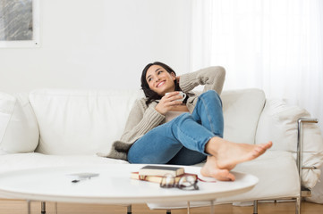 Smiling woman thinking on sofa