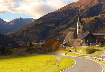 View of a road and St Maria church in Obervellach village, Austria