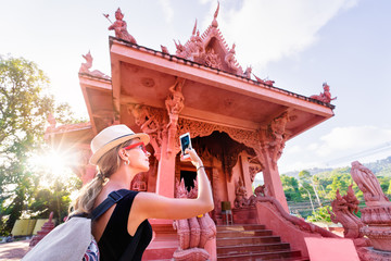 Travel by Asia. Young woman taking photo of temple on Samui Island in Thailand.