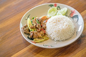 Thai food : Rice topped with stir-fried pork and holy basil on wooden table.