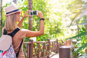 Travelling concept. Photographing adventure. Young woman taking picture on her smartphone in jungle.