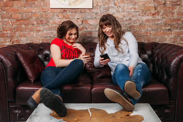 Friends using phone while sitind on sofa at living room Technology, education and friendship concept