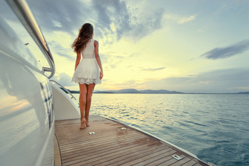 Luxury travel on the yacht. Young woman enjoying the sunset on boat deck sailing the sea.