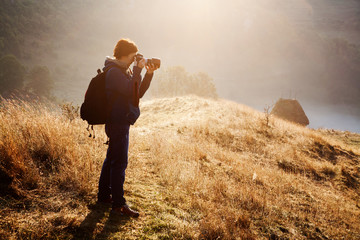 female photographer at sunrise, misty mountains