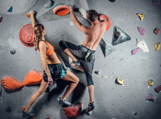 Male and female climbing on a climbing  wall.