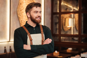 Handsome young man waiter standing in cafe.