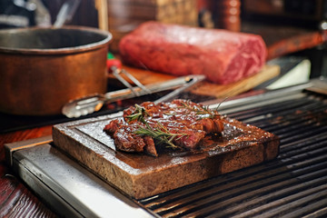 The grilled beef steak on a wooden board.