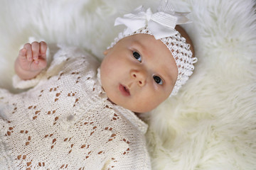 portrait of a beautiful baby girl in a white dress