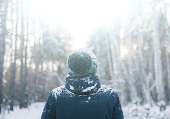 man covered in snow wearing a green beanie in the winter cold sunny forest