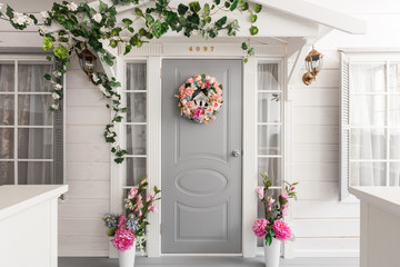 White small wooden house with gray door. spring flower decoration Fototapete