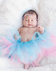 Portrait of a newborn girl with a pink-and-blue skirt and hair decoration rim on the head. Gentle photo with natural light.