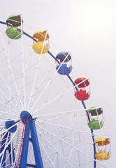 Ferris wheel on a background of grey sky