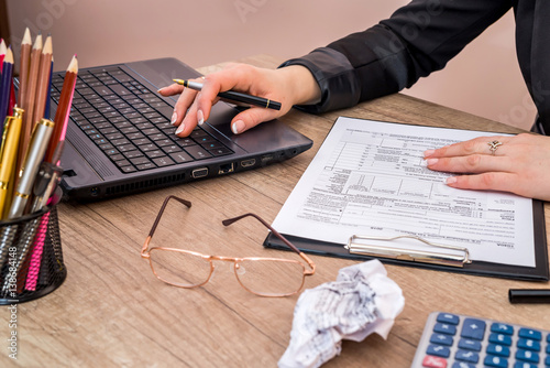 Woman use calculator with laptop for filling 1040 tax for 1040 line 28 tax table