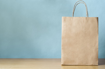 Blank Brown Carrier Bag with Handles on Light Wood Veneer Table with Blue Background