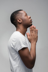 Praying african american man hoping for better. Asking God for good luck, success, forgiveness. Power of religion, belief, worship. Holding hands in prayer, looking up.