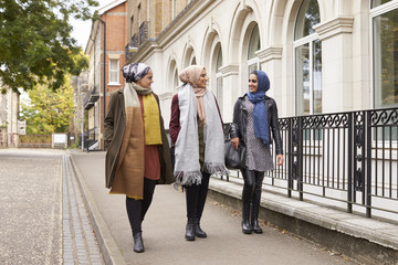 British Muslim Female Friends Walking In Urban Environment