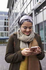 British Muslim Woman Texting On Mobile Phone Outside Office