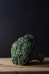 Head of Dark Green Broccoli on Wood Plank Table against Black Background