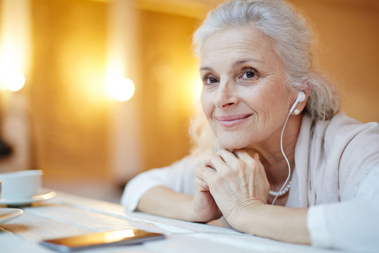 Contemporary senior female with earphones listening to music at leisure