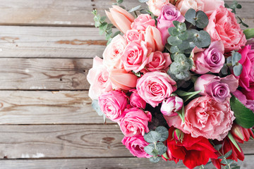 Bouquet of red roses and Other colors flowers on wooden background, copy space. top view