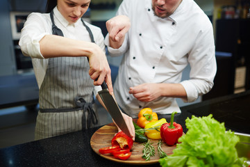 Young woman cutting fresh pepper with chef near by