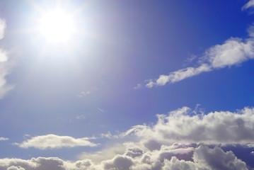 Sonne und Wolken an einem strahlend, blauen Himmel. Die Sonne sticht von oben links ins Bild.