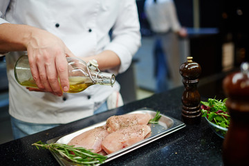 Chef pouring olive oil on raw chicken steak