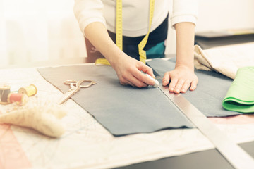 woman tailor working. marking the fabric with chalk