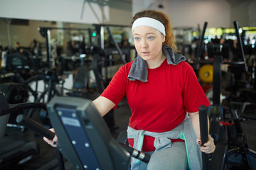 Portrait of cute overweight woman with red hair doing weight loss exercises on machines in gym