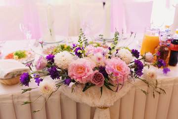 Bouquet of violet pinks and pink roses lies on white dinner table