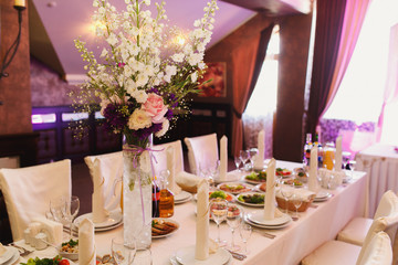 Tall glass vase with white and violet flowers stands in the middle of reach served dinner table