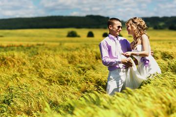 Newlyweds have fun in tall wheat