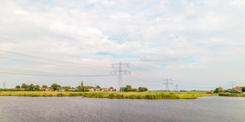 Rural Dutch scene with a small village and electricity pylons