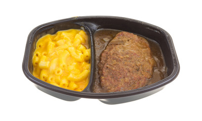 Salisbury steak meal with macaroni and cheese TV dinner isolated on a white background.