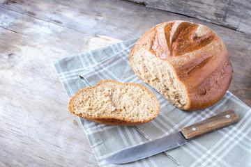 A piece of fresh crispy bread kitchen towel, kitchen wooden background