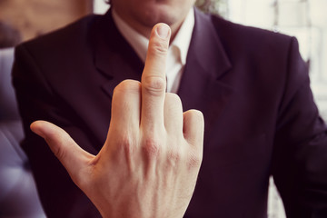 Man in business suit showing middle finger to all