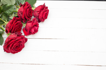 Red roses on white wooden background