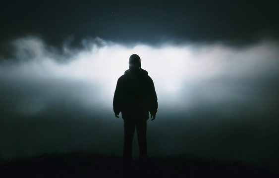 Silhouette of a man in the darkness. Night Photography. Dense fog over the river.