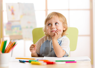 Smiling kid drawing with color pencils in day care center