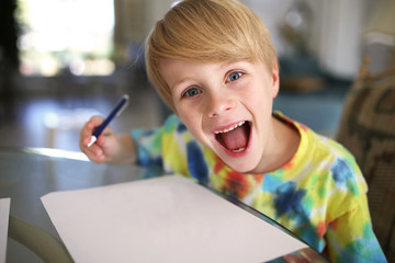 Happy Kid with Big Smile Drawing on White Paper with Pen